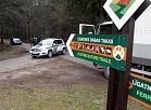 Policijas automašīna uz ceļa, kas ved uz Līgatnes dabas taku, kur no voljēra izbēdzis lācis.