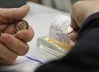 Cilvēks norēķinās par pirkumu ar eiro monētām.