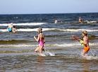 Cilvēki atpūšas un peldas Dzintaru pludmalē.