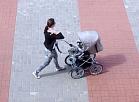 Sieviete ar bērna ratiņiem.