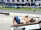 Vīrietis sauļojas Daugavas promenādē.