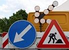 Satiksmi regulējošas ceļa zīmes uz ceļu būves automašīnas.