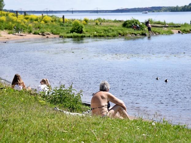 Cilvēki atpūšas Daugavas krastā.