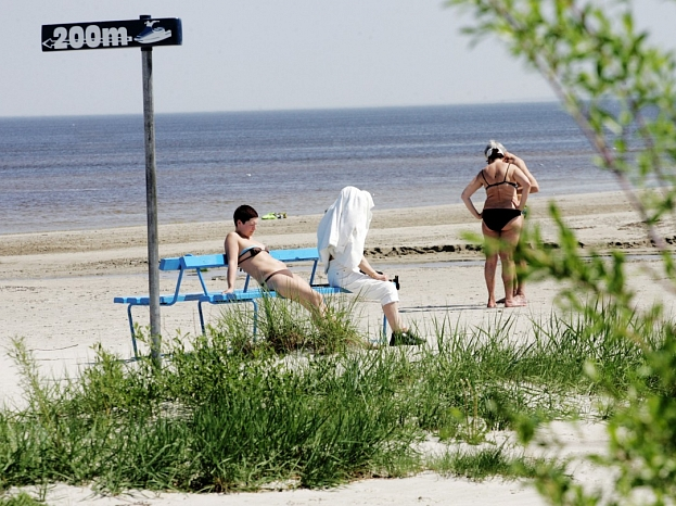 Cilvēki sauļojas pie jūras Kauguros.
