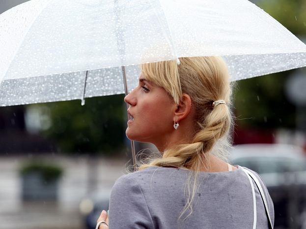Sieviete lietus laikā.