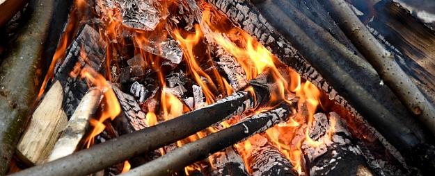 Lecot pāri ugunskuram, vīrietis ar koka zaru gūst galvas traumu